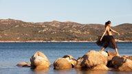 Frau stolziert über Steine im Meer