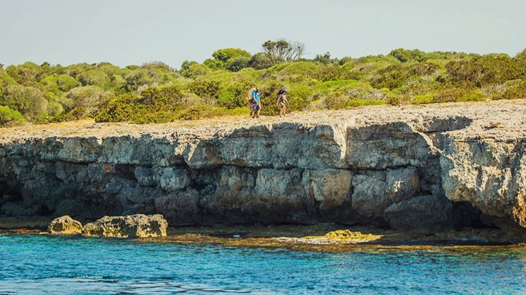 Zwei Urlauber wandern entlang der menorquinischen Küste