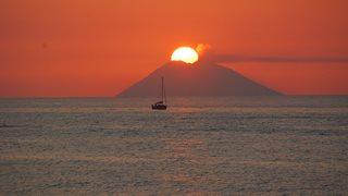 Die Sonne geht in der Ferne hinter der Vulkaninsel Stromboli unter