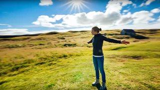 Urlauberin genießt die Sonnenstrahlen und idyllische Natur Islands