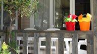 Sandspielzeug mit Eimern stehen auf der Terrasse einer Ferienwohnung
