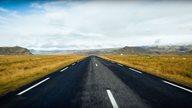 Flache Straße verläuft durch die isländische Landschaft