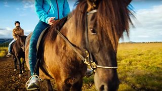 Zwei Urlauberinnen reiten auf lokalen isländischen Pferden