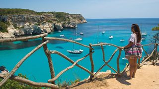 Eine Urlauberin genießt den Ausblick auf die türkise Bucht von Cala Macarella