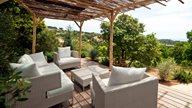 Gartenmöbel auf einer Terrasse in Gartenanlage eines Ferienapartments