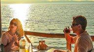 Ein Paar sitzt in einem griechischen Restaurant bei Sonnenuntergang am Meer