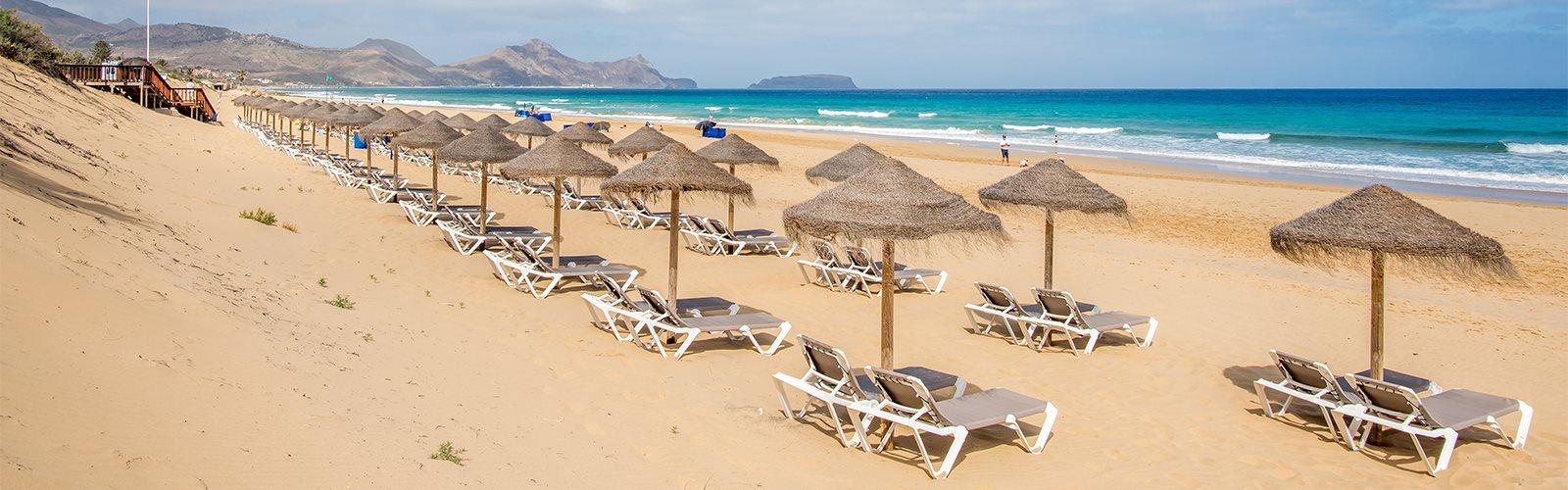 Sandstrand am Meer auf Porto Santo mit Liegen und Sonnenschirmen