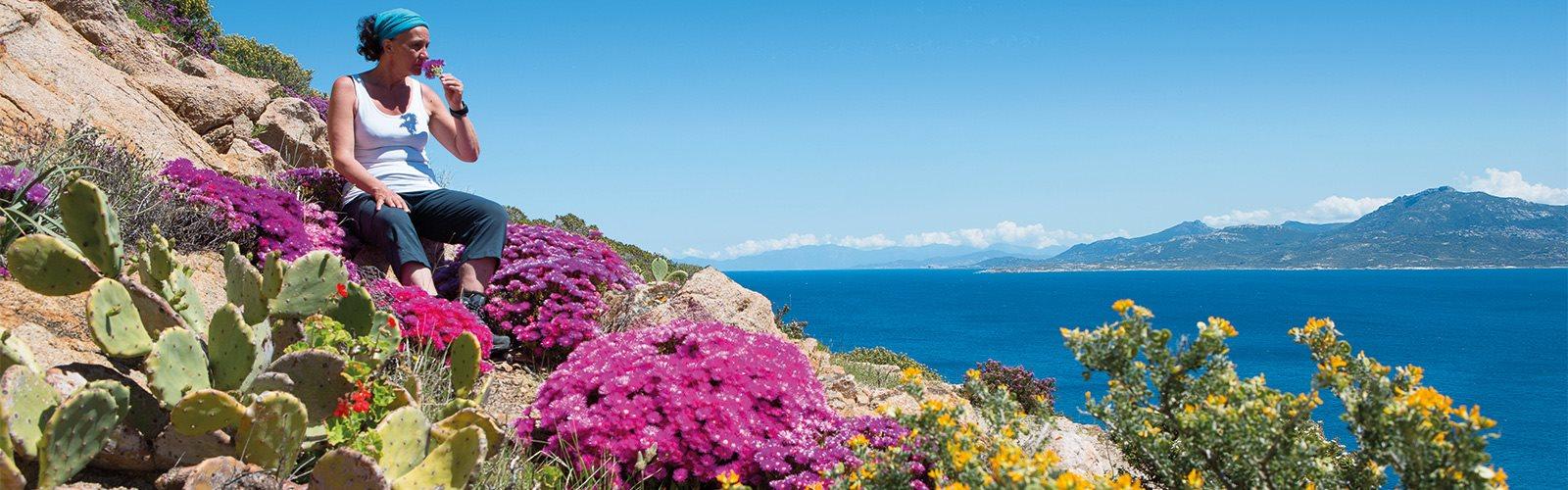 Frau sitzt auf Felsen in Korsika und riecht an Blume